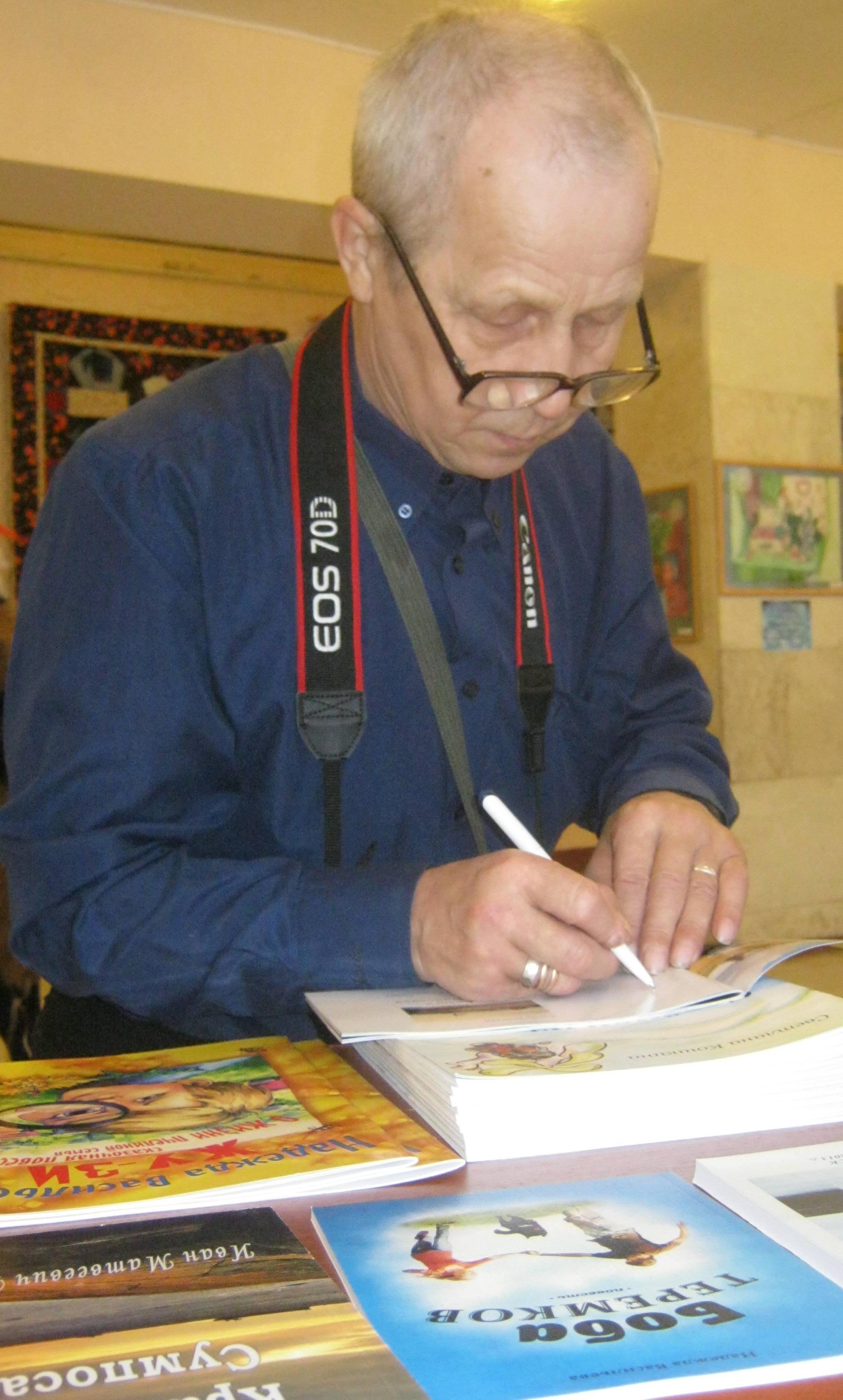 Виктор Дрягуев подписывает авторский фотоальбом. 20 декабря 2014 г. Фото С. Кошкиной